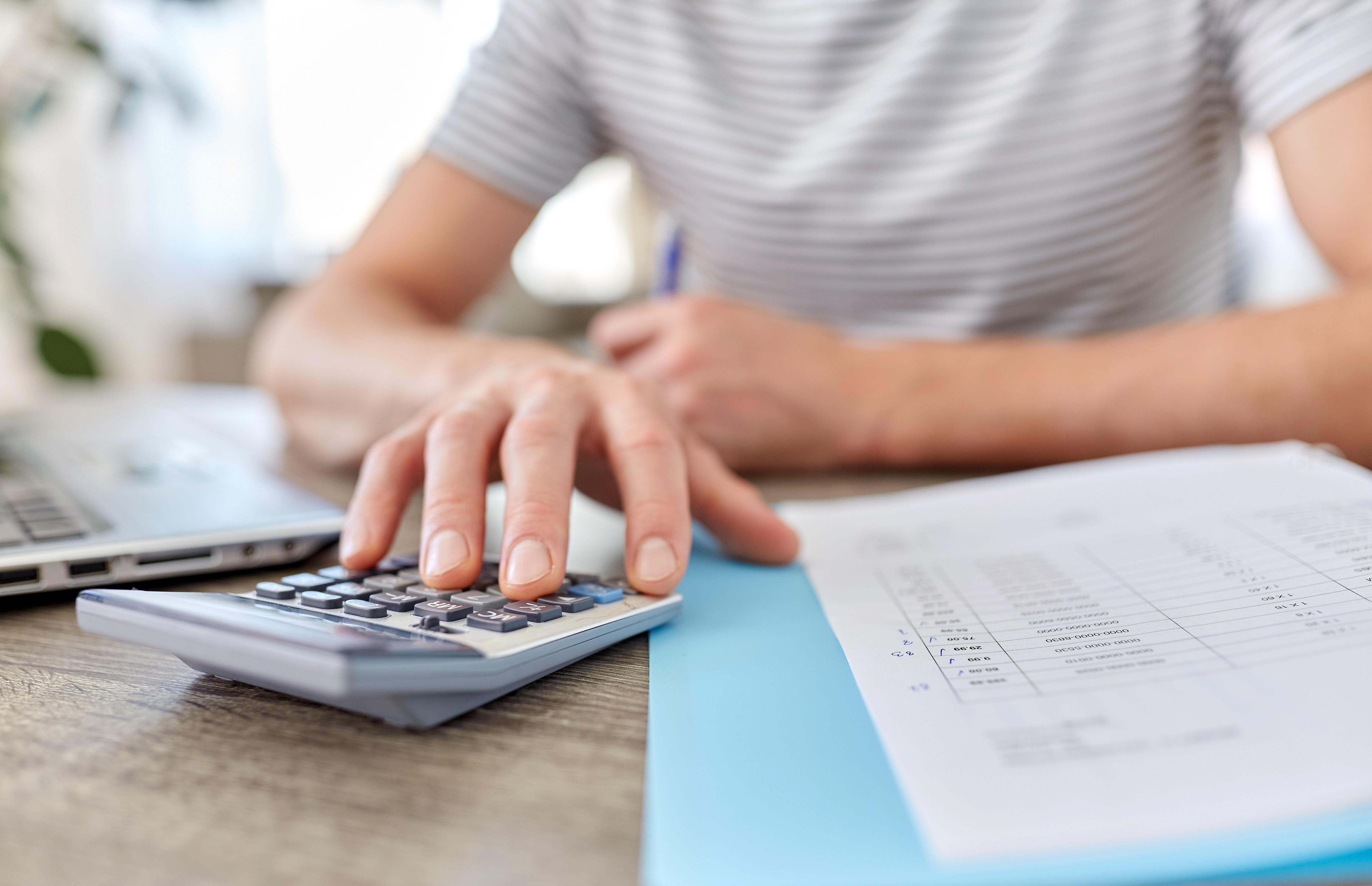 Ein Mann berechnet mit einem Taschenrechner die Rate.
